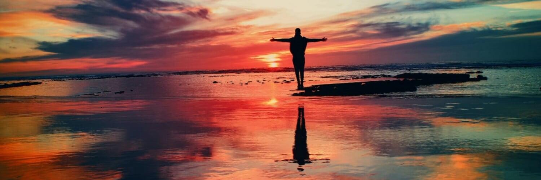Mann streckt Arme aus und schaut in Sonnenuntergang