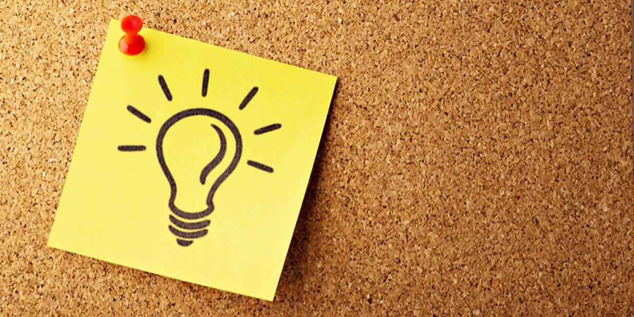 Glühbirne auf einem Zettel an einer Pinnwand