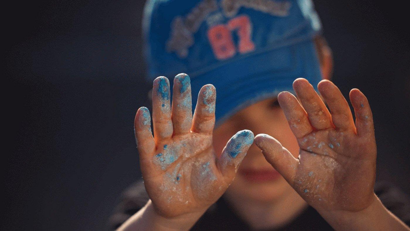 Ein Junge, der gemalt hat und seine bunten Hände in die Kamera hält